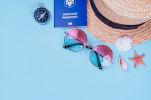 Travel Flatlay With Biometric Passport, Gradient Round Sunglasses, Straw Boater Hat And Compass On The Bright Blue Background. Decorated With Sea Shells And Starfish.