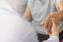 Parkinson And Alzheimer Female Senior Elderly Patient Hand With Physician Doctor Exam In Hospice Care Room.