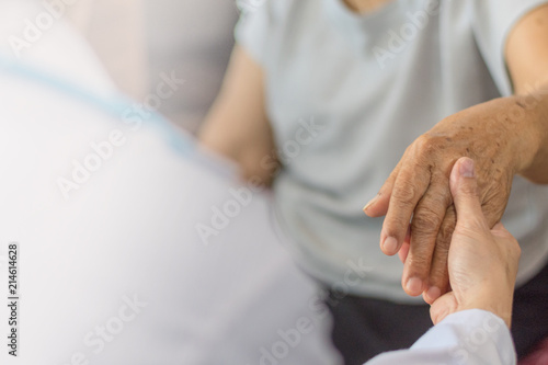 Parkinson and alzheimer female senior elderly patient hand with physician doctor exam in hospice care room Wallpaper Mural