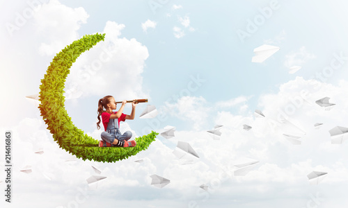 Concept of careless happy childhood with girl on green moon - fototapety na wymiar