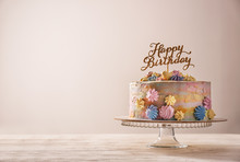 Stand With Delicious Birthday Cake On Table Against Light Background