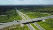 aerial shot road junction with many moving cars in the middle of green forest