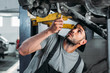workman with equipment repairing car in mechanic shop