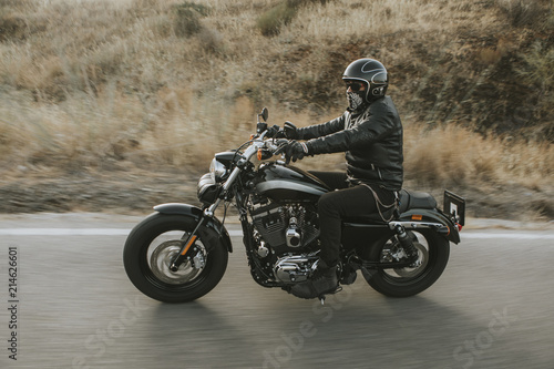 Man in black clothes riding a black classic American motorcycle in a road Fototapeta
