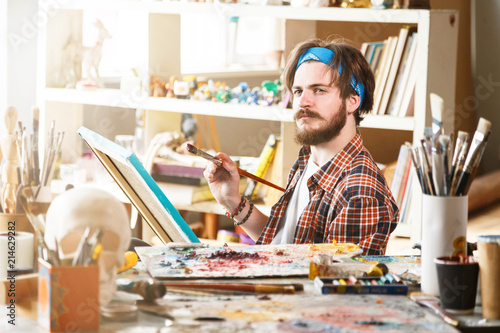 Keuken foto achterwand Koken Young dark-haired caucasian male artist in blue bandana sitting and holding brush in his sunny studio