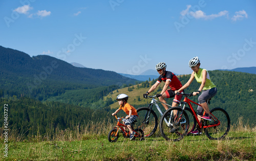 Sporty active family cyclists, mother, father and kid cycling on bikes on grassy hill. Carpathian mountains, blue summer sky on background. Healthy lifestyle, traveling and happy relations concept.