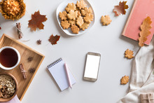 Top View And Flat Lay Of Autumn Composition Background. Notebook, Cup Of Hot Tea, Book, Autumn Leaves And Flowers, Cinnamon Cookies On White Background.