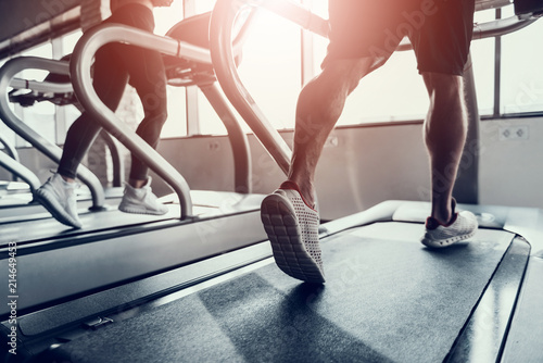 Fotografie, Obraz Close up. Man and Young Woman on Treadmills in Gym