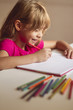 girl makes drawings in schoolbook with paints and colored pencils