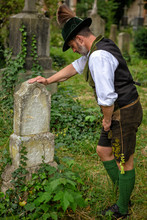 Bavarian Man Standing In Front Of Grave