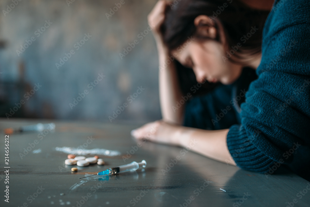 Fototapeta Drug addict sitting at the table with narcotics