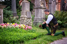 Bavarian Man Kneeling In Front Of Grave