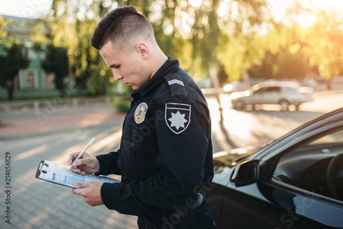 Male police officers writes a fine on the road Fotobehang