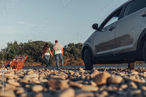 Obraz Happy Traveler Couple on Picnic into the Sunset with SUV Car - fototapety do salonu