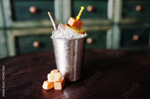 Photo  Alcoholic cocktail with sweets and candies in small silver bucket at bar table