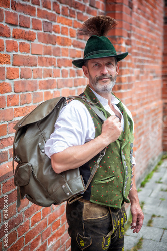 Foto bavarian man standing outside with backpack