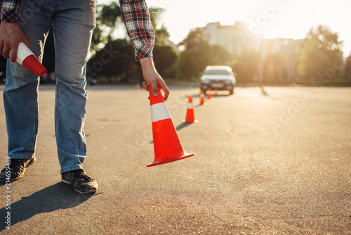 Instructor sets the cone, driving school concept