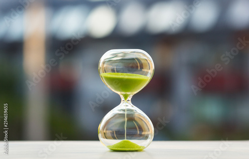 Canvastavla  Close-up, hourglass with green sand on a blurred background