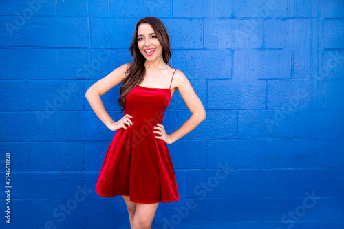 Fotografie, Obraz  Fun spirited confident hopeful and lively female in a colorful bright red dress