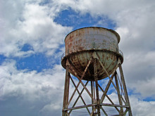 Rusty Water Tower Against Clou...