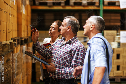 Fotografía Team of customs managers and warehouse worker checking list and inventory on the shelf in storehouse