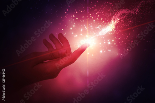 Photo  A female hand giving a stream of magical energy on a dark abstract background
