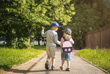 Two Young Children Friends Boy And Girl Hold Hands And Walk Along Road In The Summer Green Park On Sunny Afternoon. Child Friendship. Children Are Walking In The Park