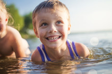 Portrait Of Beautiful Children Laugh And Bathe In The Sea. Boy Smiles And Swims In Lake. Good Mood Kids On Summer Lake.