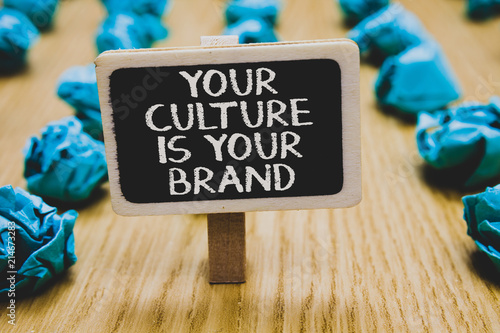 Fototapeta Handwriting text writing Your Culture Is Your Brand. Concept meaning Knowledge Experiences are a presentation card Stand blackboard with white words behind blurry blue paper lobs woody floor. obraz