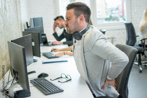 Cuadros en Lienzo Businessman suffering from backache in office