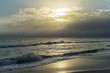 Waves Break on a Sandy Beach Before a Cloudy Sunset