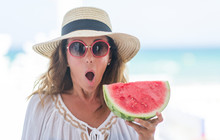 Middle Age Brunette Woman By The Sea Eating Watermelon Scared In Shock With A Surprise Face, Afraid And Excited With Fear Expression