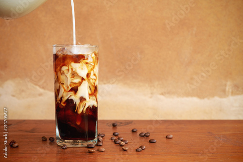 Photo  Pouring milk into a glass of homemade cold brew coffee on wooden table
