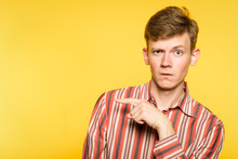 Look There. Funny Comic Man Pointing Sideways With A Hand. Portrait Of A Young Guy On Yellow Background. Free Space For Advertisement.
