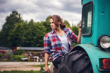 Young Beautiful Girl Is Working On A Tractor In A Field On A Farm, An Unusual Job For Women, Gender Equality Concept