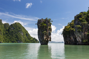 Phang Nga, Thailand. Rock in the Andaman sea. The James Bond Island (Khao Phing Kan, Koh Tapu). Blue sky, white clouds and green water
