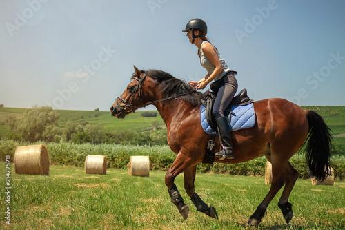 Tablou Canvas Frau model Reiterin reitet auf Pferd auf Wiese in der Natur bei Sonnenschein im