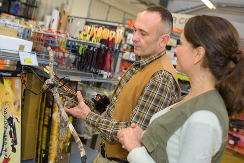 Man in shop looking at crossbow Fotobehang
