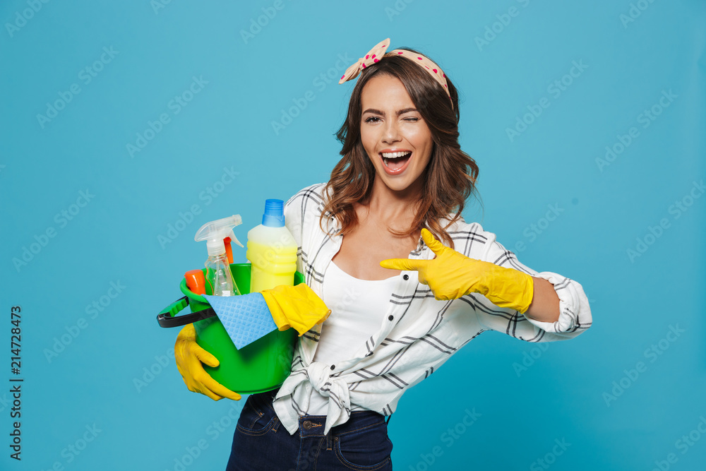 Fototapety, obrazy: Photo of pleased young housemaid 20s wearing yellow rubber gloves for hands protection holding bucket with cleaning supplies, isolated over blue background