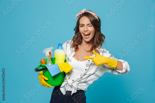 Photo of pleased young housemaid 20s wearing yellow rubber gloves for hands prot Fototapet