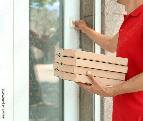 Valokuva Young man with pizza boxes ringing the doorbell outdoors