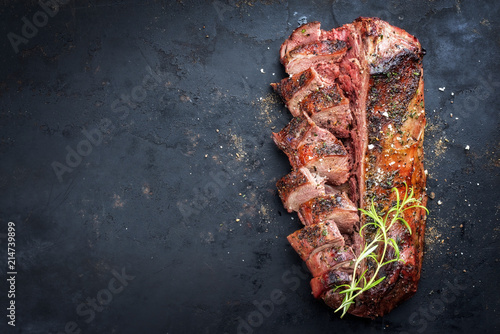 Aluminium Prints Grill / Barbecue Traditional barbecue aged saddle of venison marinated as top view on an old rustic board with copy space left