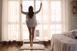 Morning of beautiful young woman opening curtains in bedroom