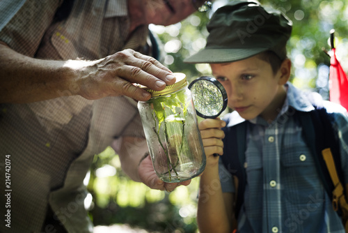 Boy examining a plant with a magnifying glass Fototapeta