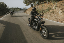 Man Riding A Black Classic American Motorcycle On The Road In The Mountains.
