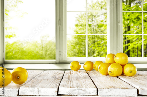 fresh yellow lemon on desk and window background with summer garden. Free space for your glass.