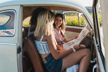 Young Women With Map Inside Of Vintage Car