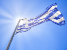 Official Flag Of Greece Waving On A Blue Sky And Sunlight Rays.