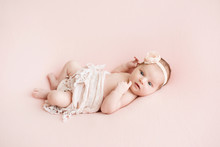 Newborn Girl On A Pink Background. Photoshoot For The Newborn. 7 Days From Birth. A Portrait Of A Beautiful, Seven Day Old, Newborn Baby Girl