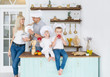 Happy caucasian family in white caps with two kids is in home kitchen.